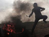 Палестинец кидает камень во время столкновений с израильскими солдатами на границе Израиля и Сектора Газа
