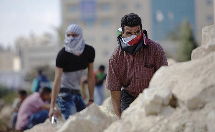 Палестинцы во время столкновений с израильскими полицейскими рядом с городом Рамалла