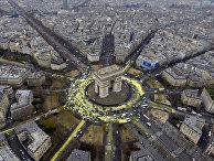 Улицы вокруг Триумфальной арки в Париже, выкрашенные в желтый цвет активистами Greenpeace