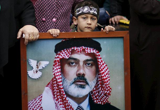 Мальчик с портретом лидера ХАМАС Исмаила Хании на параде в Газе в честь 28-летия основания движения