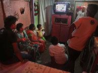 Индийская семья смотрит телевизор, где объявляют результаты выборов