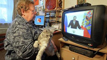 Жительница Челябинска смотрит телевизионную трансляцию послания президента РФ В.Путина к Федеральному Собранию