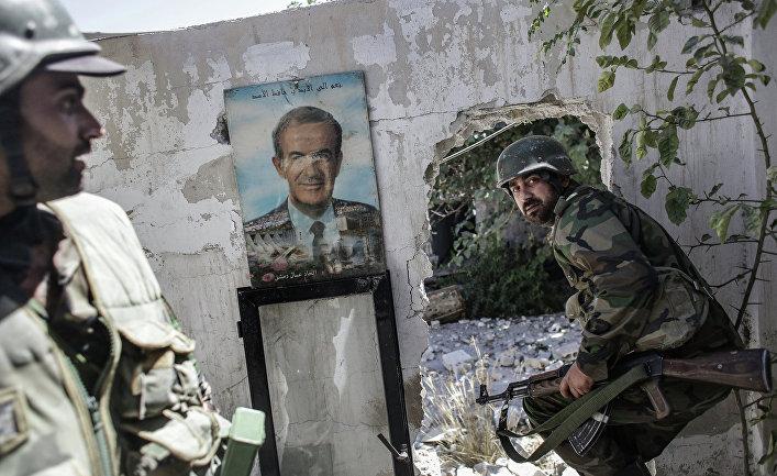Военнослужащие сирийской правительственной армии около портрета экс-президента Сирии Хафеза Асада во время военных столкновений в районе Барзе провинции Дамаск, январь 2015 года