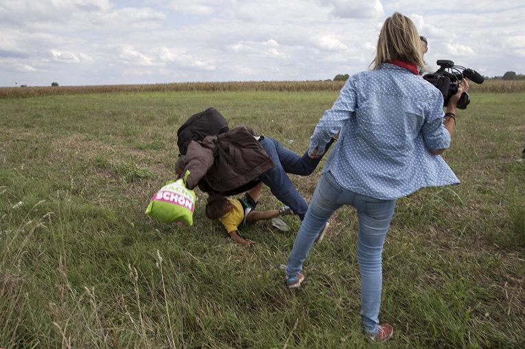 Женщина-оператор N1TV ставит подножку беженцу на границе Сербии и Венгрии
