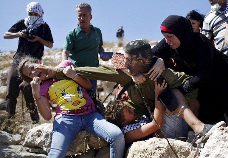 Палестинцы пытаются помешать израильскому солдату задержать мальчика во время протеста против еврейских поселений в деревне Наби Салех