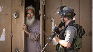 Пожилой житель города Аль-Рам закрывает свой магазин во время столкновений протестующих с израильской полицией