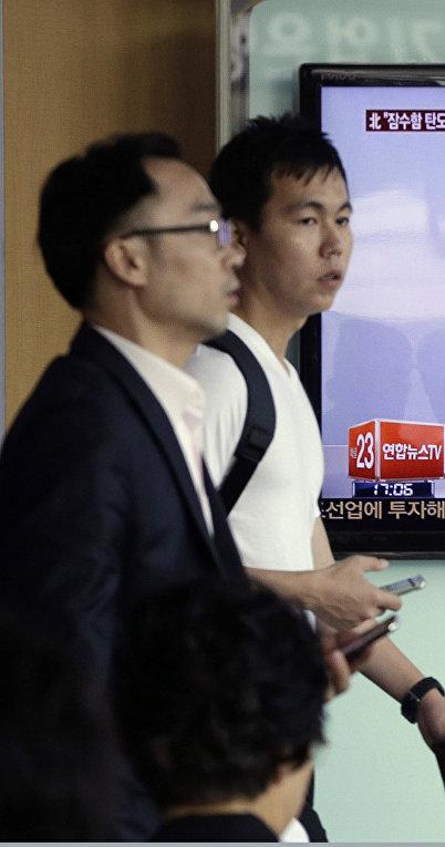 Телевидение в Сеуле демонстрирует кадры, на которых изображены Ким Чен Ын и ракета, предположительно запущенная в КНДР с подводной лодки