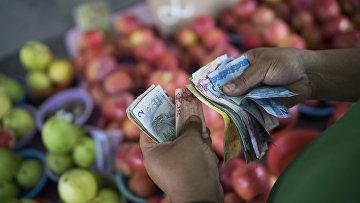 Продавец фруктов в Рио-да-Жанейро считает деньги