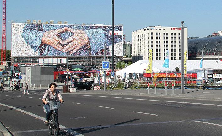 """Агитационный плакат с изображением """"фирменного жеста"""" Меркель у центрального вокзала Берлина"""