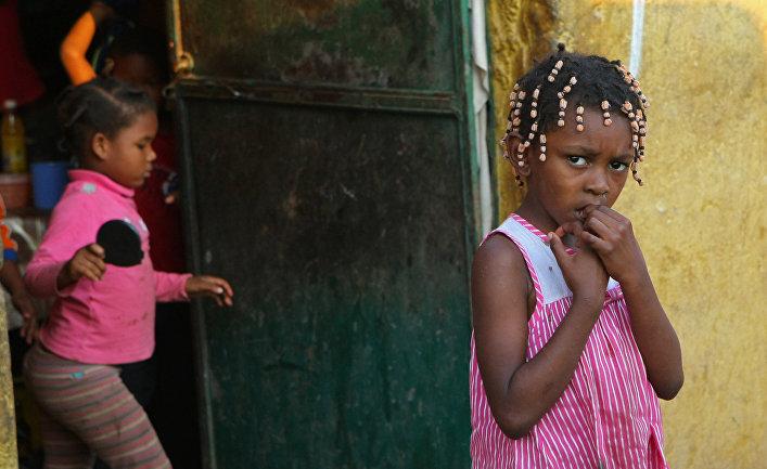 Дети стоят возле дома на улице одного из жилых районов города Луанда