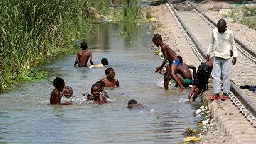 Дети купаются возле железной дороги в городе Луанда