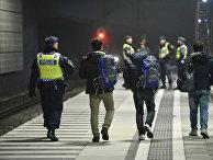 Полицейский сопровождает мигрантов в Швеции