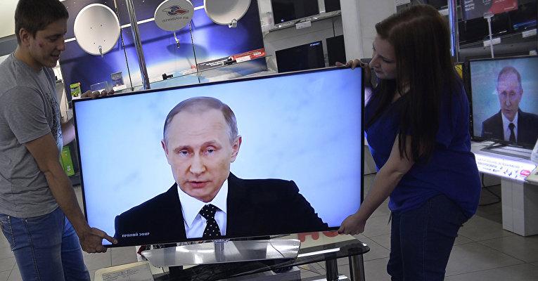 Работники магазина электроники в Москве устанавливают телевизор