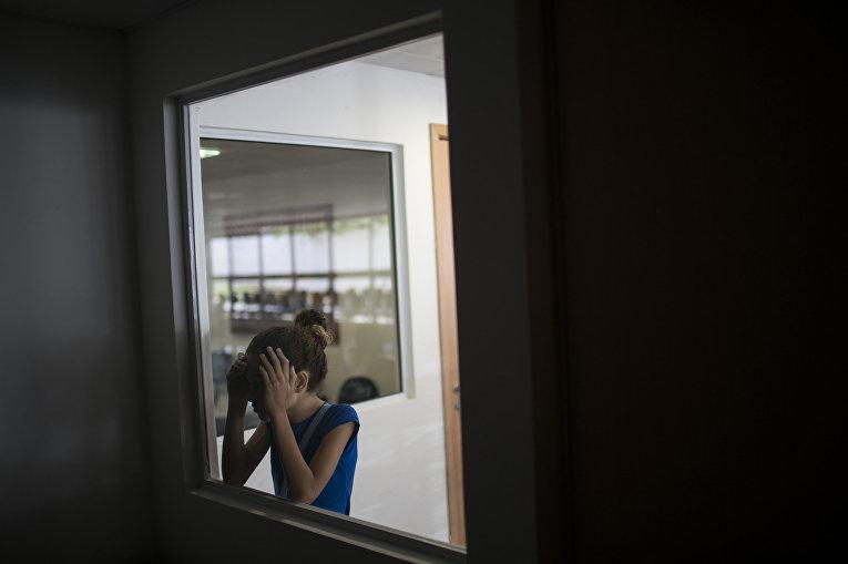 Дженнифер Карине смотрит в помещение, где ее брат Хуан Педро, рожденный с микроцефалией проходит обследование