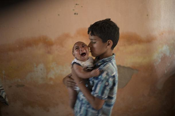10-летний Элисон нянчит своего двухмесячного брата Хосе Уэсли, который родился с микроцефалией
