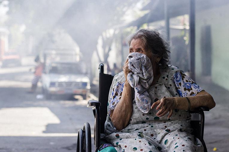 Женщина закрывает лицо от химикатов, которыми сотрудники городских служб обрабатывают местность для защиты от комаров вида Аedes Аegypti, переносящих вирус Зика