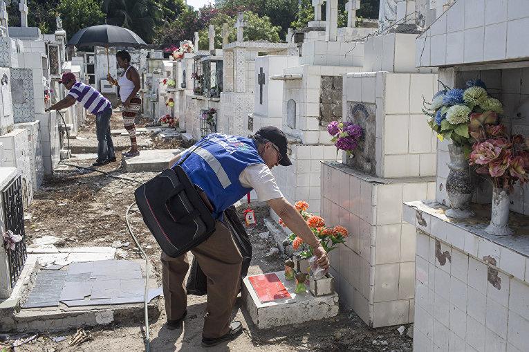 Медицинский работник опустошает вазы на кладбище в рамках операции по уничтожению комаров вида Аedes Аegypti, переносящих вирус Зика