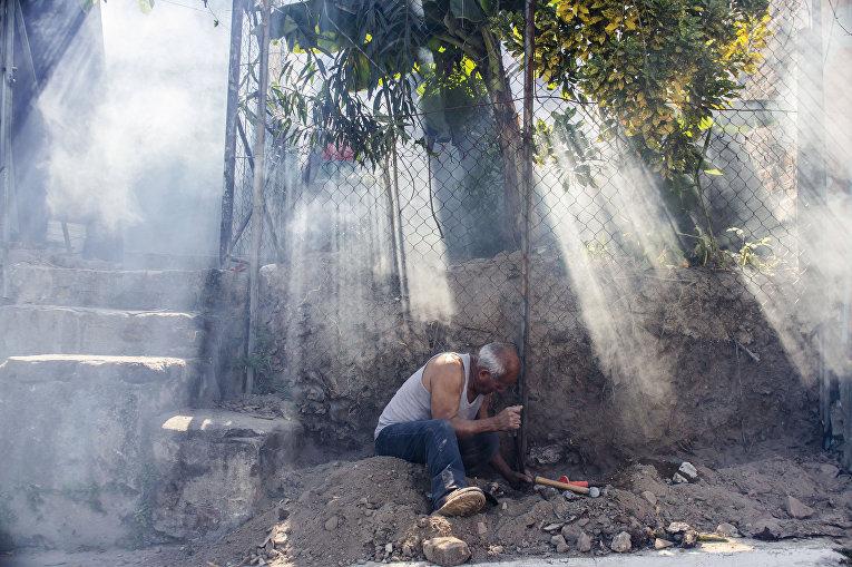 Мужчина работает среди облака инсектицидов, распыленных городскими службами для борьбы с комарами вида Аedes Аegypti, переносящих вирус Зика