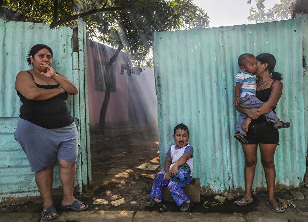 Женщины с детьми ждут пока их дом обработают инсектицидами против комаров вида Аedes Аegypti, переносящих вирус Зика
