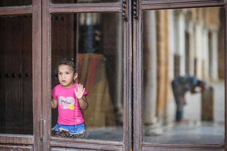 Девочка смотрит на мужчину, умывающегося после службы в местной мечети