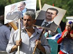 Сириец держит плакаты с изображениями Владимира Путина и Башара Асада на акции в поддержку российских военных действий в Сирии, Дамаск