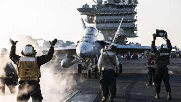 Моряки направляют истребитель F/A-18C Hornet на взлетную полосу авианосца «Гарри Трумэн»
