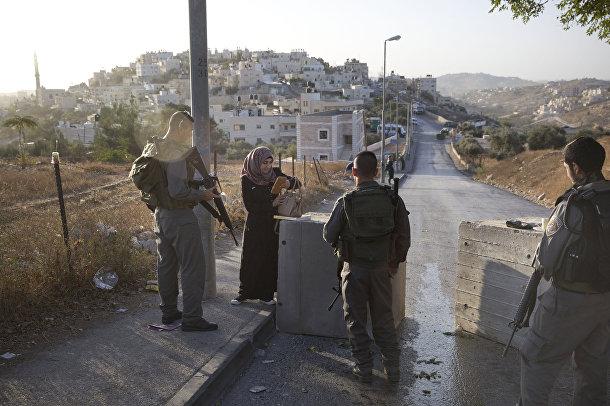 Израильские полицейские проверяют документы у палестинки рядом с бетонными блоками, установленными на востоке Иерусалима