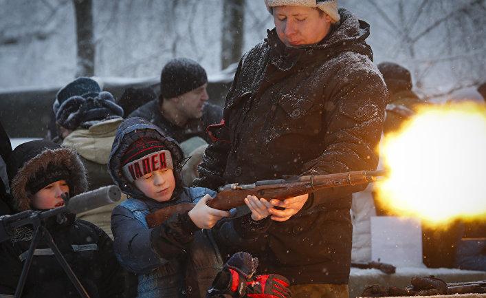 Мальчик стреляет из винтовки во время оружейной выставки в Санкт-Петербурге