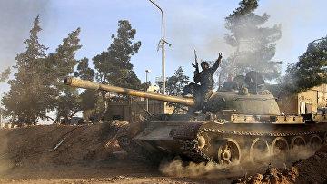 Доброволец, сражающийся на стороне сирийской армии едет на танке в городе Рекка