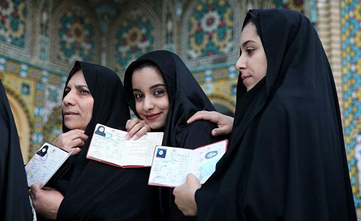 Иранские девушки показывают паспорта на избирательном участке на выборах в парламент и в совет религиозных экспертов в Иране