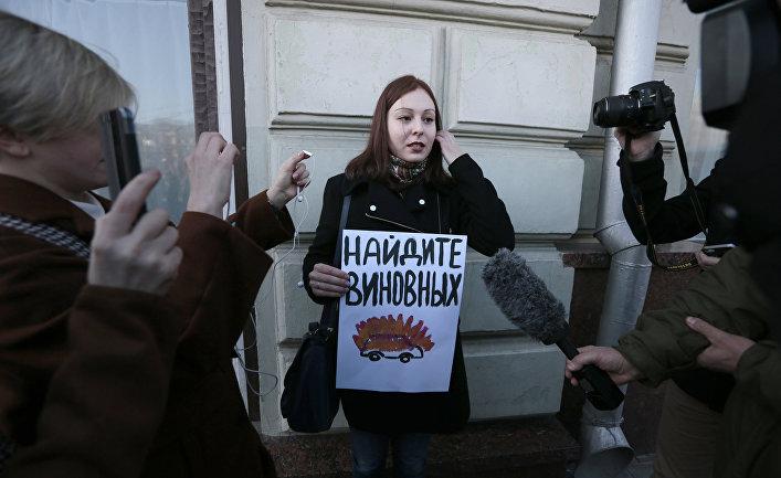 Активист отстаивающий права человека с плакатом, призывающим найти виновных в инциденте с нападением на журналистов