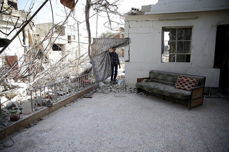 Мальчик в разрушенном доме в пригороде Дамаска