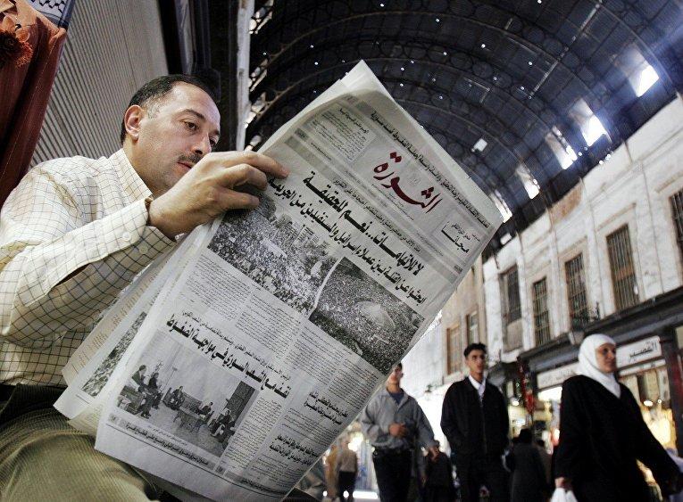 Сириец читает газету на рынке в Дамаске