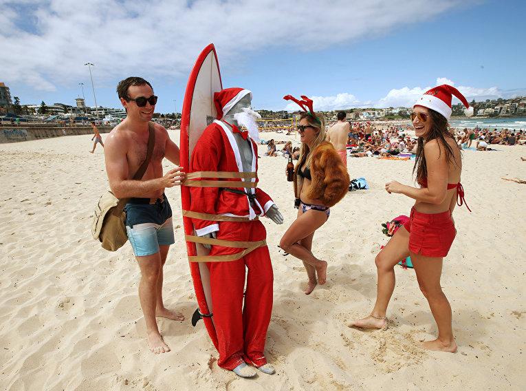 Отдыхающие на пляже  привязали фигуру Санты Клаума к доске для серфинга