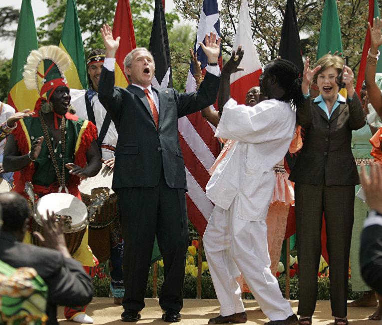Бывший президент США Джордж Буш вместе со своей женой танцуют восточно-африканские танцы