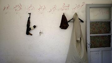 Рубашка и автомат Калашникова на стене штаб-квартиры повстанцев на окраине Алеппо