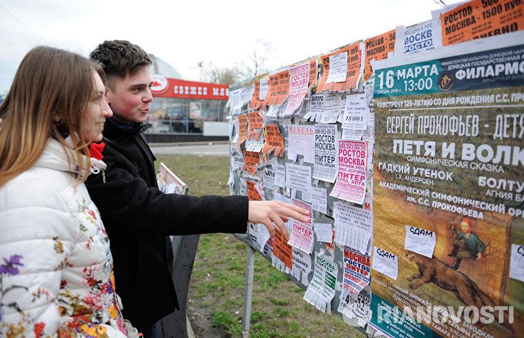 Юные жители города читают объявления на уличном стенде в Донецке