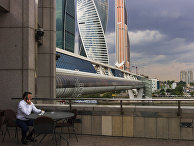 Мужчина сидит в кафе на набережной Москва-реки с видом на небоскребы «Москва-Сити»