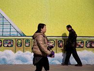 Люди проходят мимо рисунка на стене торгового центра в Пекине