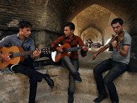 Молодые люди играют на музыкальных инструментах рядом с Мостом 33 арок в Исфахане