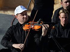 Скрипач Павел Милюков выступает на концерте симфонического оркестра петербургского Мариинского театра в Римском амфитеатре сирийской Пальмиры