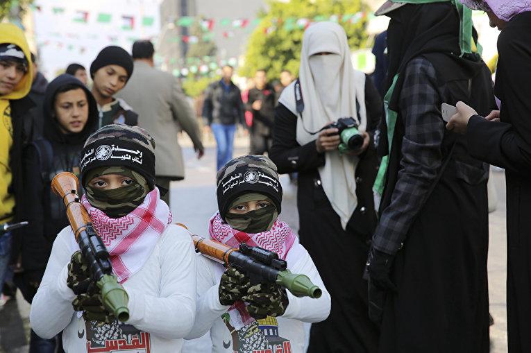 Дети с игрушечным оружием о время парада в Газе в честь 28-летия основания движения ХАМАС
