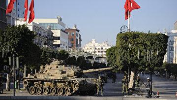 Солдаты стоят возле танка на улице Туниса