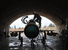 """Сирийский летчик осматривает самолет МИГ-21 сирийских ВВС перед вылетом на авиабазе """"Хама"""""""