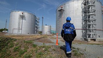 Сотрудник Новосибирской нефтебазы компании «Газпром нефть» возле резервуаров для хранения топлива
