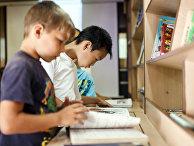 Школьники читают книги в автобусе передвижной библиотеки во дворе школы в хуторе Клетский Волгоградской области.