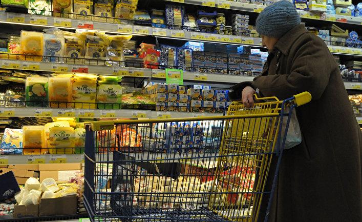 Пожилая женщина выбирает сыр в супермаркете