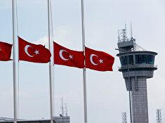 Приспущенные турецкие флаги на фоне вышки в аэропорту имени Ататюрка в Стамбуле, Турция. 29 июня 2016