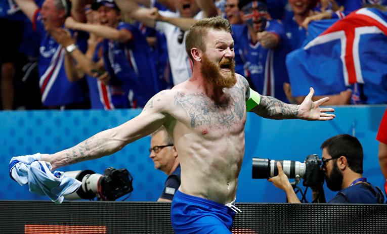 Игрок сборной Исландии Арон Гуннарссон празднует победу в матче со сборной Австрии на Евро-2016