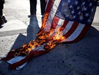 Активисты сжигают флаг во время акции протеста против произвола полиции